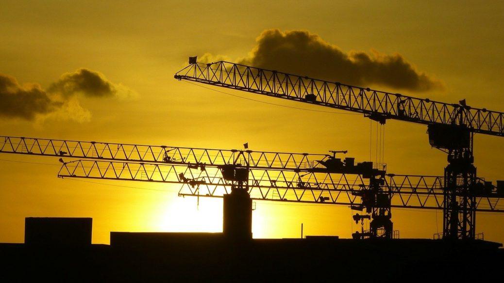 Výstavba bytů - západ slunce - stavební jeřáby